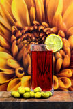 Glass of vermouth with olives on a wood table. On a gigantic flower Royalty Free Stock Photo