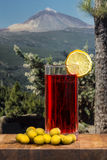 Glass of vermouth with olives on a wood table. Looking at the mountains Royalty Free Stock Images