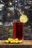 Glass of vermouth with olives on a wood table. Over a dawn near the river Royalty Free Stock Photography
