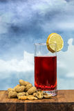 Glass of vermouth with peanuts on a wood table. Glass of vermouth with  peanuts on a wood table over a blue sky Royalty Free Stock Image