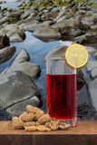Glass of vermouth with peanuts on a wood table. Over marine rocks on the coast Stock Photo