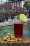 Glass of vermouth with  peanuts on a wood table. Over a view of a river Stock Photography