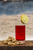 Glass of vermouth with peanuts on a wood table. Glass of vermouth with  peanuts on a wood table over waves crashing Stock Images