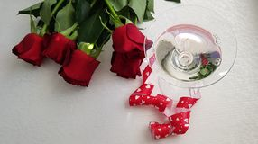 Glass with vermouth stading wrapped with red hearts ribbon stock photography