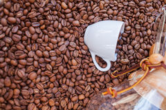 Glass vessel and coffee mug on pile of coffee beans. Background. Royalty Free Stock Photo