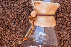 Glass vessel dip in pile of coffee beans. Background. Stock Photography