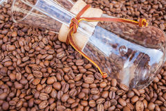 Glass vessel dip in pile of coffee beans. Background. Stock Image