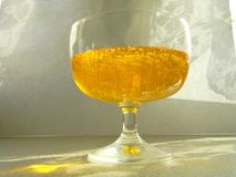 Glass vessel with honey. The sun`s rays shine on the glass. Glass vessel with honey.  The sun`s rays illuminate the vessel Stock Photo