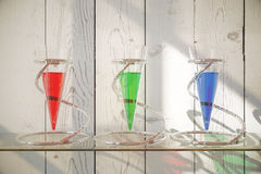 Glass vessels with liquid. Three glass vessels with colorful liquid on shelf and wooden background. 3D Rendering Royalty Free Stock Images