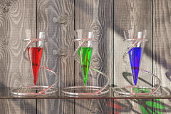 Glass vessels on wooden background. Three glass vessels with colorful liquid on shelf and textured dark wooden background. 3D Rendering Stock Photography