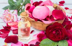 Rose petals and essential oil. Spa aromatherapy. Glass vial with rose essential oil and rose petals on Wooden bowl on a  white wooden background Royalty Free Stock Photography