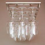 Glass vinexponeringsglas på stångupphängning hänga för stångexponeringsglas Många tomma rena exponeringsglas som hänger i stången Royaltyfri Bild