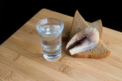 Glass with vodka and appetizer with sprat and bread. Black background. royalty free stock photo