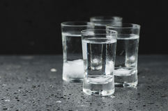 A glass of vodka on the black table Stock Photos