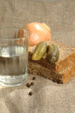 Glass of vodka, bread and pickled cucumber Royalty Free Stock Photos