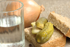Glass of vodka, bread and pickled cucumber Stock Image