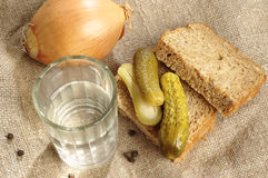 Glass of vodka, bread and pickled cucumber Royalty Free Stock Images