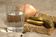 Glass of vodka, bread and pickled cucumber Royalty Free Stock Photography