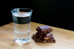 Glass with vodka and chocolate on wooden table and black background royalty free stock photos