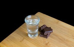 Glass with vodka and chocolate on wooden table and black background stock image