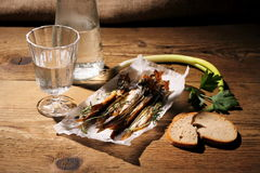 Glass of vodka with dried capelin and bread Stock Images