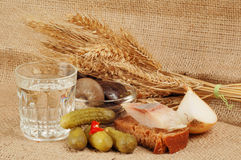 Glass of vodka and food. Glass of vodka with pickles, bread, fish, onion, bowl of mushrooms, bundle of wheat against a burlap background Royalty Free Stock Photos