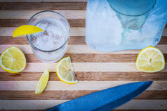 Glass of vodka. With ice cubes and lemons around Royalty Free Stock Photo