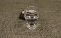 A glass of vodka, lard, bread on the table. There is a place to fill stock photo
