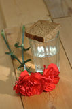 Glass of vodka and red carnations on a wooden table Stock Images