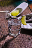 Glass of vodka shot with fresh lime Royalty Free Stock Photography