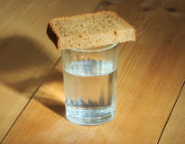Glass of vodka and a slice of bread on a wooden table Stock Image
