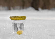 Glass of vodka and a snack in the snow. Stock Photo