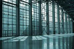Glass wall. Large hall of a modern industrial building with glass wall, columns and sunlight spots on the stone floor Stock Images