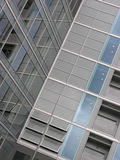 Glass wall. Inside corner of a modern building mostly made of glass and windows, neutral gray or even titatium hue, reflections on the glass surfaces. Skyscraper Stock Image