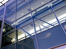 Glass wall. Reflecting sky from a glass wall of a modern office building Stock Images