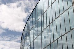 Glass wall of city hall Almere. Clouds are reflecting in the glass wall of the city hall of Almere in the Netherlands royalty free stock photo