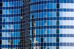 Glass wall of modern office building with sky reflections Royalty Free Stock Photography