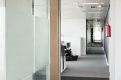 Glass wall and narrow passageway in office Royalty Free Stock Images