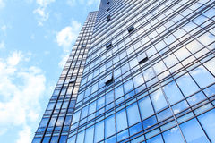 Glass wall of office building. With reflection of clouds Stock Images