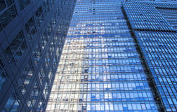 Glass wall of office building. With reflection of clouds Stock Photos