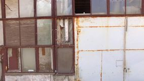 Glass wall of a building with broken windows. The glass wall of the old building with broken windows and rusted ceilings stock video
