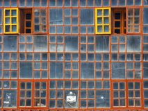 Glass wall from old windows with a vintage wooden frames, two frames bright yellow color open, glass bluish color. Glass wall from old windows with vintage Royalty Free Stock Images