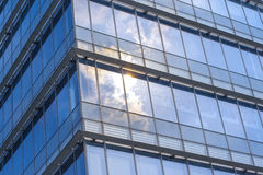 The glass wall reflect the sun and cloud Royalty Free Stock Images