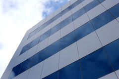 Glass wall of a skyscraper. Glass wall of a skyscraper and sky in the daytime Stock Photography