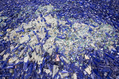 Glass waste in recycling facility. Blue bottles Royalty Free Stock Photos