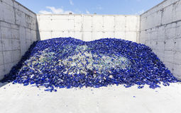 Glass waste in recycling facility. Blue bottles Royalty Free Stock Images
