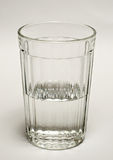 Glass with water. Glass thick glass tumbler half filled with water Royalty Free Stock Image