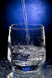 Glass with water. Dark blue background Stock Images