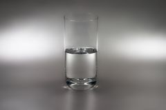 Glass of water. Half-empty (or half-full) glass of water on silver background stock image