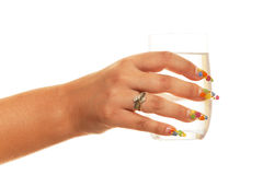Glass of water. A woman hand with a glass of water; isolated on the white background Stock Image